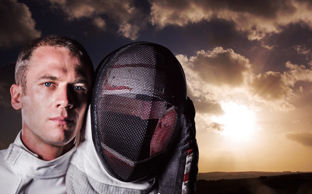 swordsman: Close-up of swordsman holding fencing mask against cloudy sky