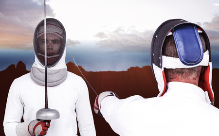 fencing sword: Man wearing fencing suit practicing with sword against composite image of landscape