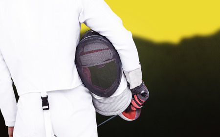 swordsman: Rear view of swordsman holding fencing mask and sword against blurred mountains Stock Photo