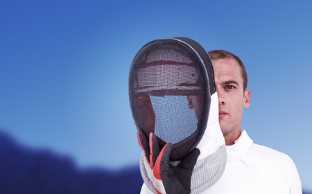 swordsman: Swordsman holding fencing mask against scenic view of blue sky