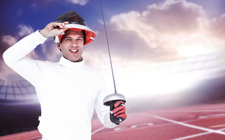 fencing sword: Man wearing fencing suit practicing with sword against race track Stock Photo