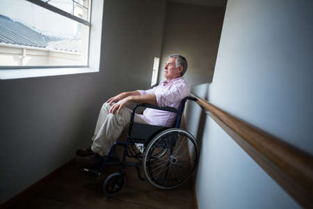 looking through: Senior man sitting on wheelchair and looking through window at home