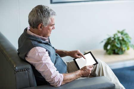 medical man: Senior man in medical clinic using digital tablet
