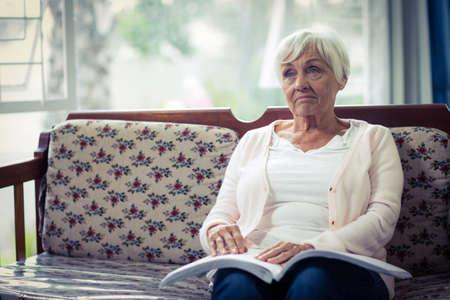 braile: Pensativo mujer ciega que se sienta en el sofá con el libro en braille en la vuelta