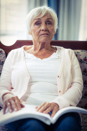 braille: Pensive blind woman sitting on sofa with braille book on lap