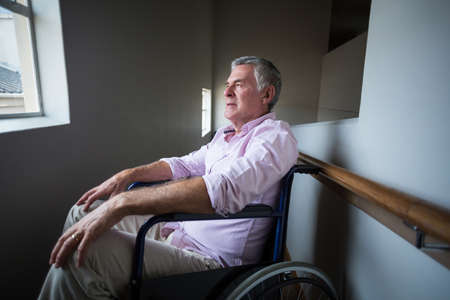 looking through window: Senior man sitting on wheelchair and looking through window at home