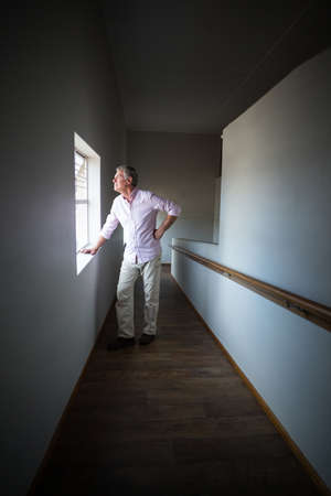think through: Senior man looking through window at home