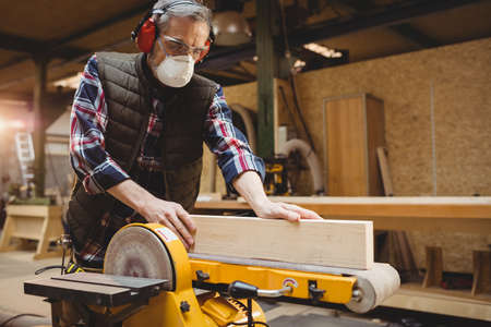 anti noise: Carpenter sawing a plank of wood in carpentry