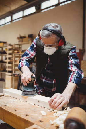 anti noise: Carpenter sanding down a plank of wood in carpentry