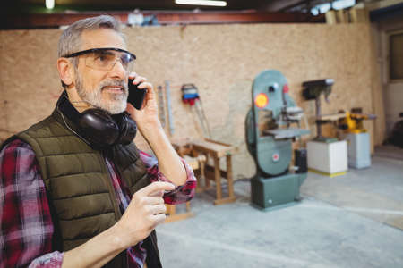 anti noise: Carpenter on the phone in carpentry