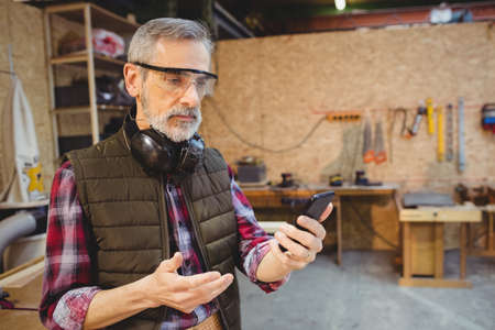 anti noise: Carpenter using his smartphone