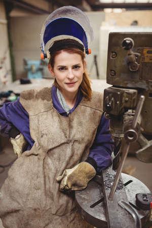 only mid adult women: Portrait of woman welder posing beside a machine in a workshop
