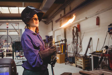 flaming torch: A portrait of a young woman welder with a flaming torch