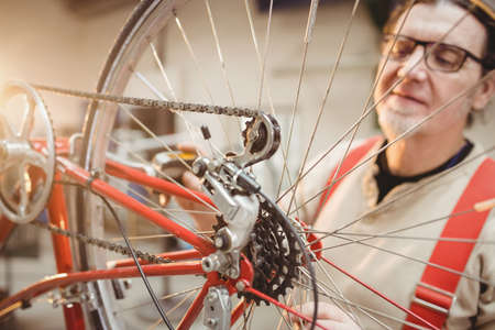 shop skill: Portrait of a bike mechanic positioned behind a bike wheel in a workshop