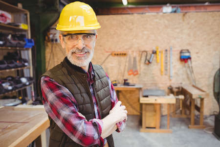 crossing arms: Smiling carpenter crossing arms in front of camera in a workshop LANG_EVOIMAGES