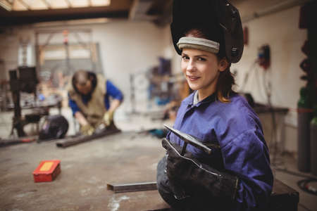 protective workwear: Female welder in protective workwear with colleagues working in background LANG_EVOIMAGES