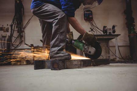 man power: Welder cutting metal with grinder in workshop LANG_EVOIMAGES