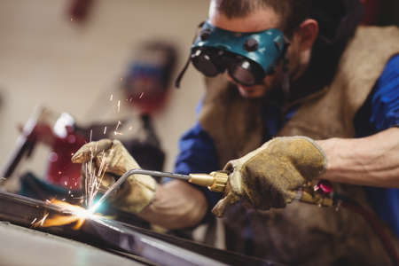 1 adult only: Close-up of a male welder using a welder torch in workshop