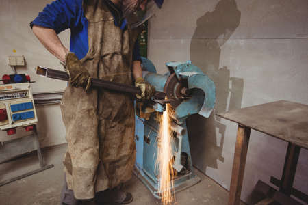 forge: Portrait of male welder using a sander in forge
