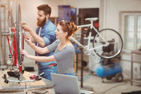 two women and one man: Duo of colleague repairing a bicycle in a workshop