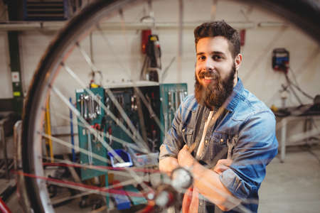 crossing arms: Portrait of hipster crossing arms while standing behind a bicycle wheel in a workshop