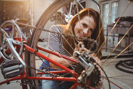 workwoman: Woman repairing a red bicycle in a workshop