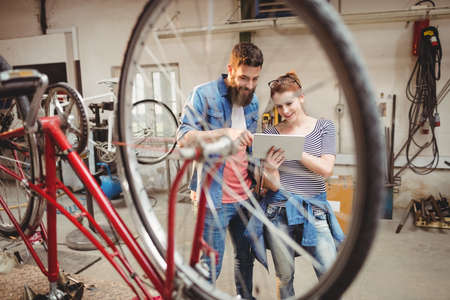 repairer: Bicycle repairer colleagues looking at laptop in a bicycle work shop