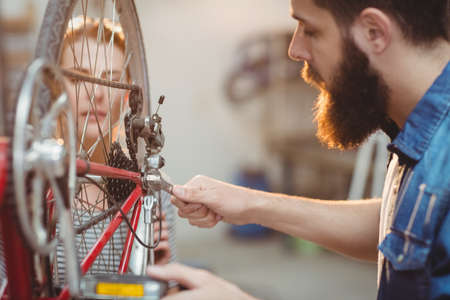 two women and one man: Side view of a hipster repairing a bicycle wheel in a workshop