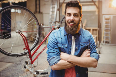 crossing arms: Portrait of hipster crossing arms while standing in front of a bicycle in a workshop