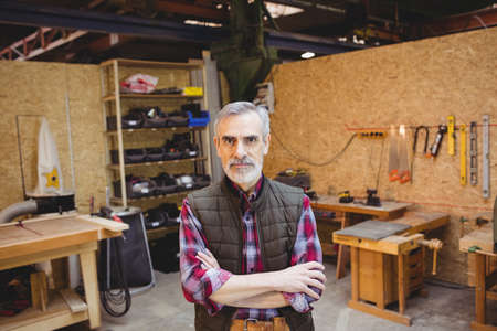crossing arms: Senior carpenter crossing arms while looking at camera in his workshop