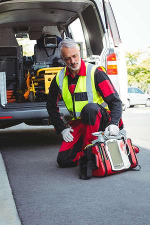 defibrillator: Ambulance man holding a defibrillator in front of ambulance car LANG_EVOIMAGES