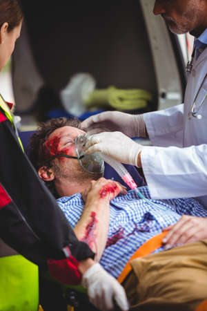 hospital trolley: Injured man receiving oxygen from a doctor in an ambulance car LANG_EVOIMAGES
