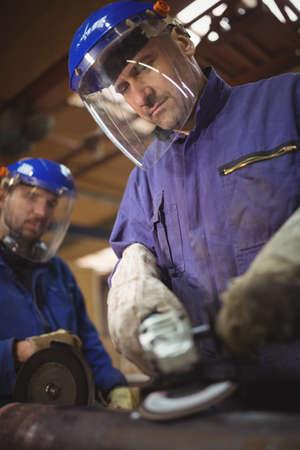 circular saw: Men cutting metal with circular saw in workshop LANG_EVOIMAGES