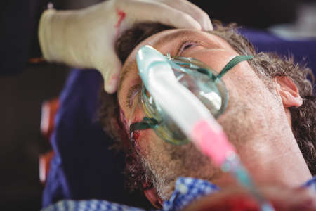 health care facilities: Close-up of an injured man wearing a gas mask in ambulance car LANG_EVOIMAGES