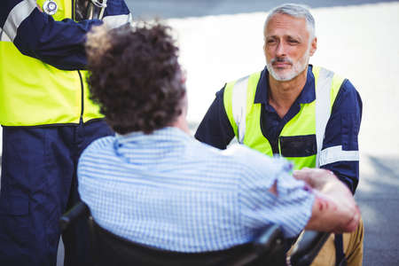 injured person: Ambulance man speaking to an injured person in wheelchair outside LANG_EVOIMAGES