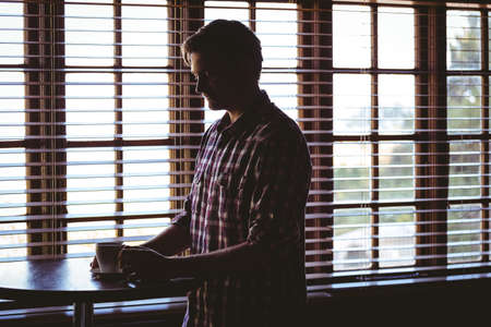 gloominess: Man drinking alone a coffee in a cafe