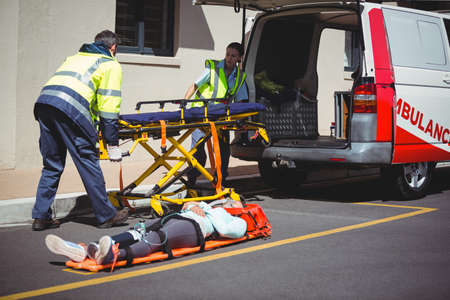 injured person: Ambulance crew preparing equipment for an injured person