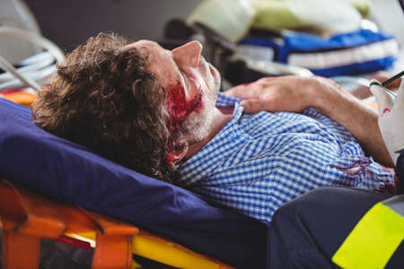 hospital trolley: Injured man lying on a stretcher in an ambulance car LANG_EVOIMAGES