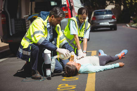 medical ventilator: Jogger lying on the road taking in hand by ambulance crew on a sunny day