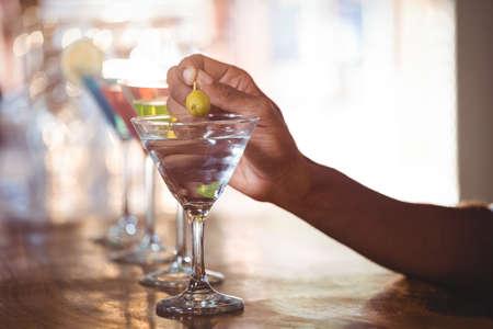 bar counter: Bartender garnishing cocktail with olive on bar counter in bar LANG_EVOIMAGES