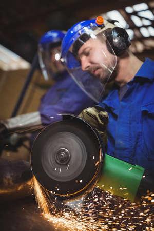 circular saw: Man cutting metal with circular saw in workshop