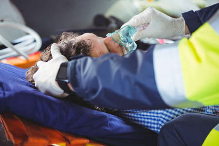 hospital trolley: Injured man receiving oxygen from ambulance man in a ambulance car LANG_EVOIMAGES
