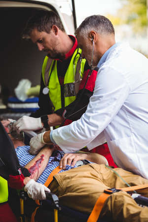 injured person: Ambulance crew and doctor taking care of an injured person in front of the ambulance vehicule LANG_EVOIMAGES