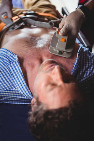 defibrillator: Injured man receiving help with a defibrillator in a ambulance car LANG_EVOIMAGES