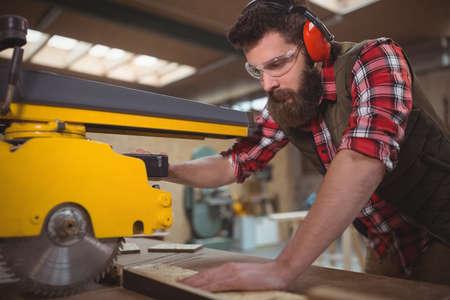 circular saw: Carpenter cutting wooden plank with circular saw in workshop