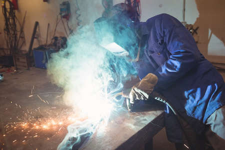 Welder working with machine in the workshop