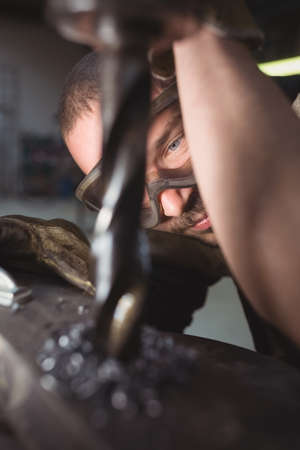 tradesman: Tradesman working with machine in the workshop LANG_EVOIMAGES