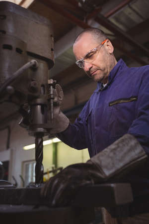 Tradesman working with machine in the workshop LANG_EVOIMAGES