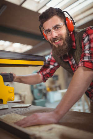 circular saw: Portrait of carpenter cutting wooden plank with circular saw in workshop
