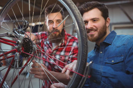 two wheel: Two mechanics repairing a bicycle wheel in their workshop LANG_EVOIMAGES